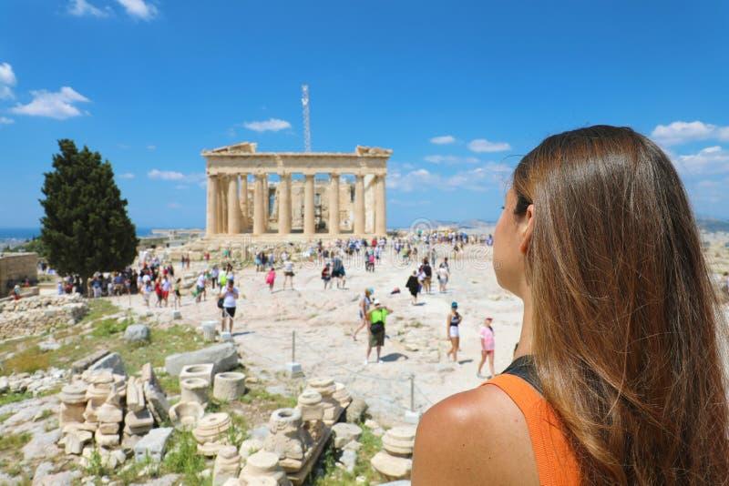 Den unga kvinnan ser Parthenon på akropolen av Aten, Grekland Den berömda gammalgrekiskaparthenonen är den huvudsakliga turisten royaltyfri fotografi