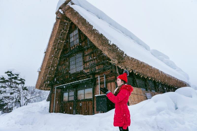 Den unga kvinnan Shirakawa-går in byn i vinter, UNESCOvärldsarv, Japan arkivfoton