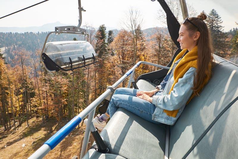 Den unga kvinnan sitter i hiss för kabelbil och ler medan blickar på arkivbild