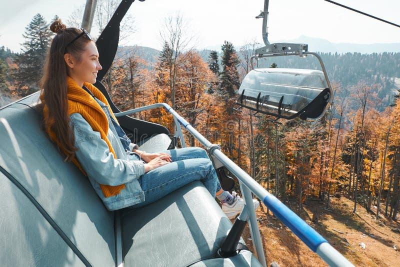 Den unga kvinnan sitter i hiss för kabelbil och ler medan blickar på höstlandskapet royaltyfria bilder