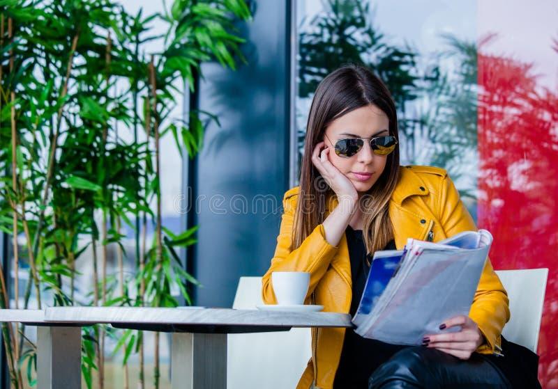 Den unga kvinnan sitter i utomhus- läs- tidskrift för kafé royaltyfri fotografi