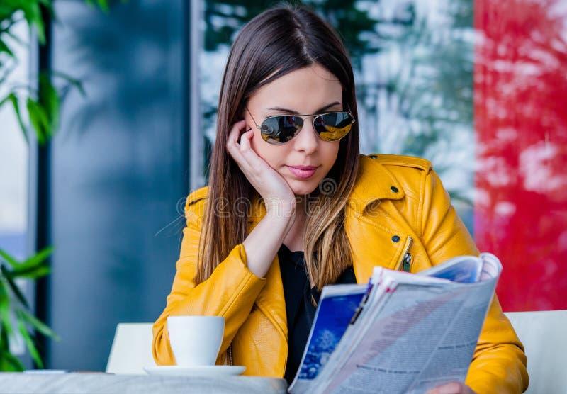 Den unga kvinnan sitter i utomhus- läs- tidskrift för kafé royaltyfria foton