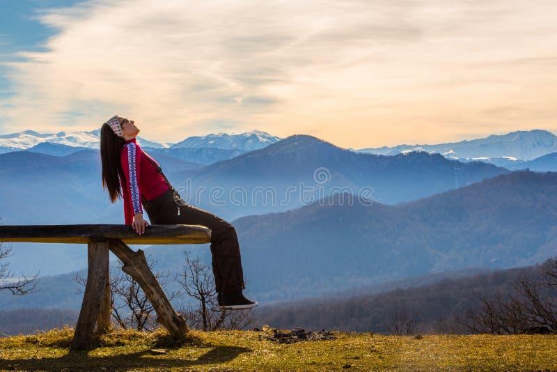 Den unga kvinnan sitter på bänk utanför och blick på det bildmässiga landskapet med berg royaltyfria foton