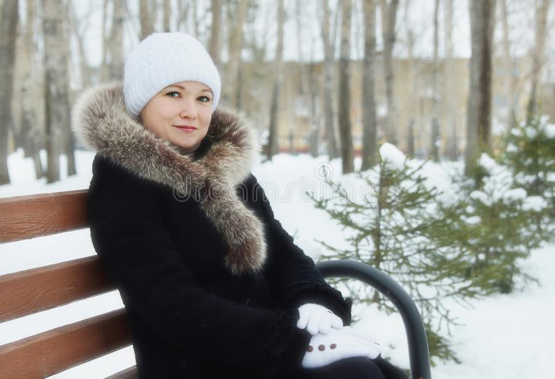 Den unga kvinnan sitter på bänken i en vinter parkerar arkivbilder