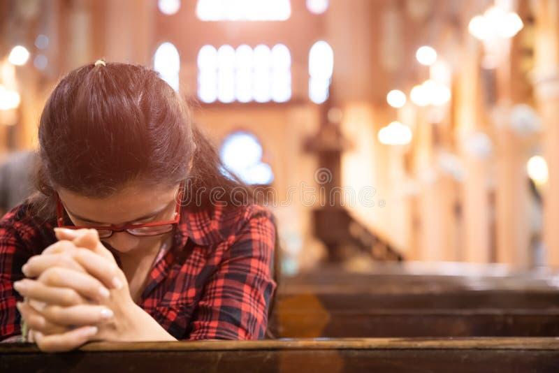 Den unga kvinnan sitter på en bänk i kyrkan och ber till guden Händer vikta i bönbegreppet för tro royaltyfria bilder