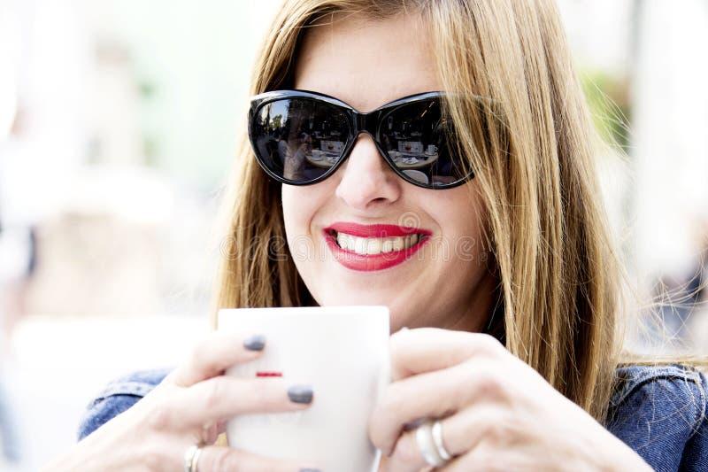 Den unga kvinnan sitter på gatakafét, dricker kaffe och ler i vår royaltyfri bild