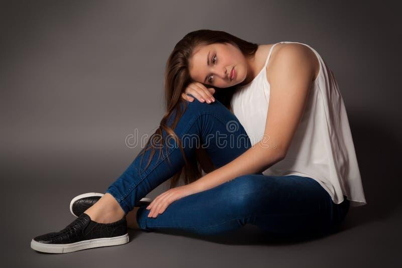 Den unga kvinnan sitter på golv arkivfoton
