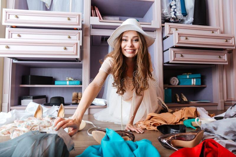 Den unga kvinnan sitter på golvet med kläder arkivbild