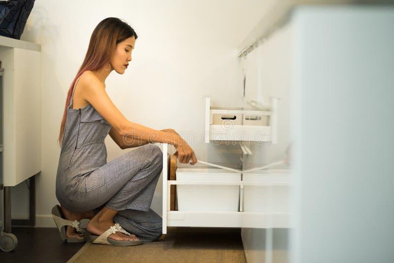 Den unga kvinnan sitter på knä i hennes öppna skåp för kök och finner till royaltyfri foto