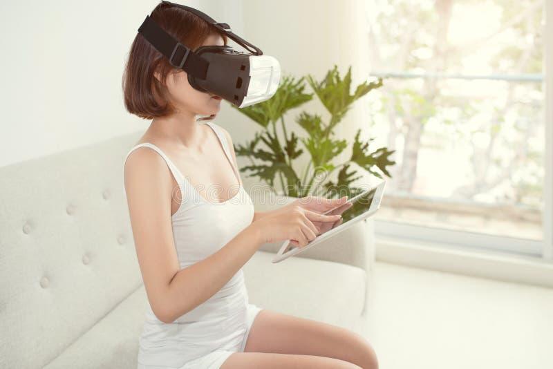 Den unga kvinnan sitter på soffan och hagyckel genom att använda vita VR-hörlurar med mikrofonexponeringsglas hemma asiatisk kine royaltyfri fotografi