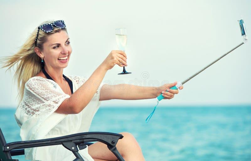 Den unga kvinnan sitter på stranden på en schäslong som dricker vin och gör fotoet mot bakgrunden av havet arkivfoto