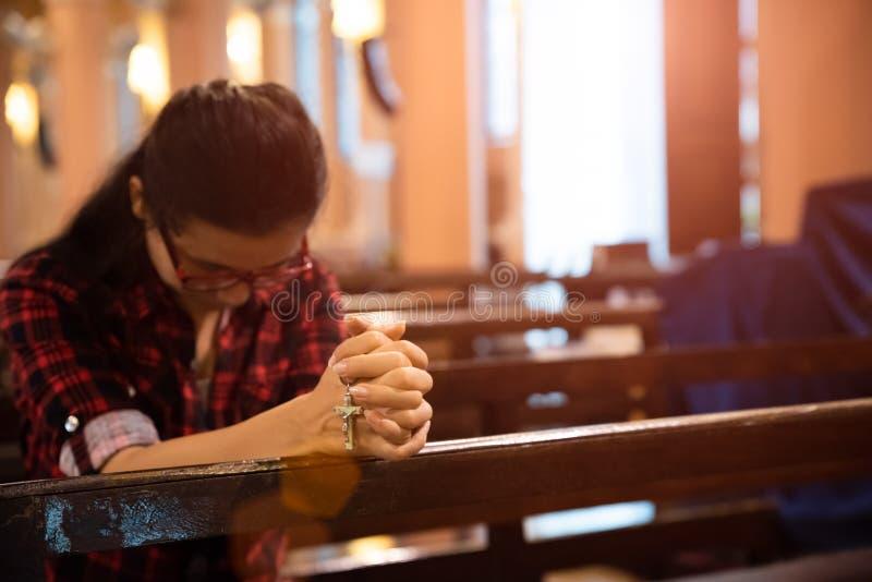 Den unga kvinnan sitter p? en b?nk i kyrkan och ber till guden H?nder vikta i b?nbegreppet f?r tro arkivbild