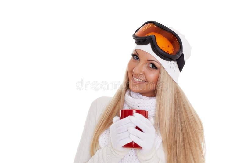 Den unga kvinnan skidar in exponeringsglas med den röda koppen arkivfoto