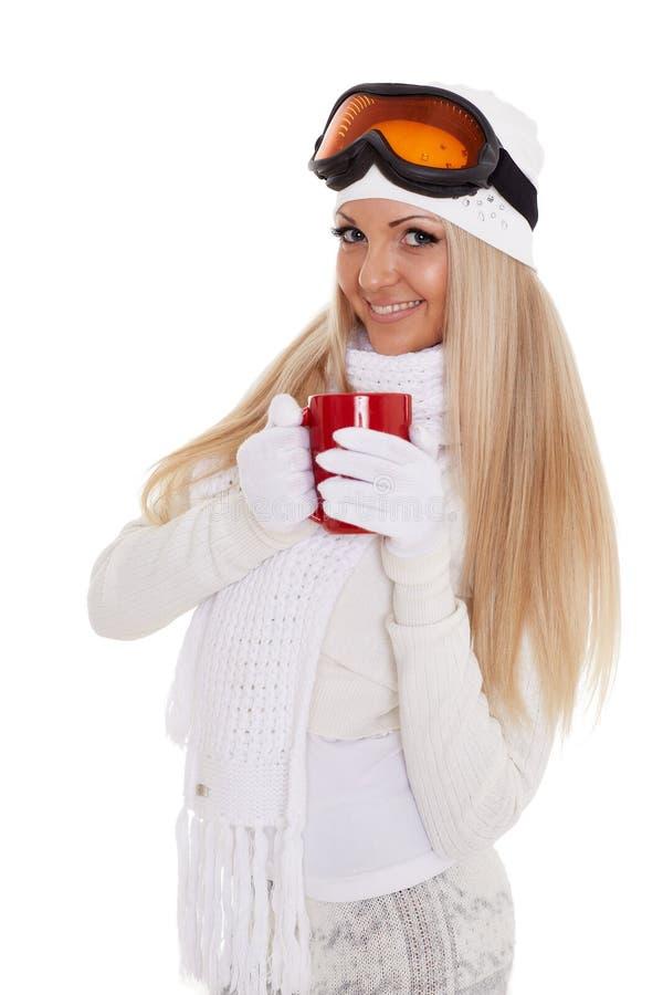 Den unga kvinnan skidar in exponeringsglas med den röda koppen arkivbilder