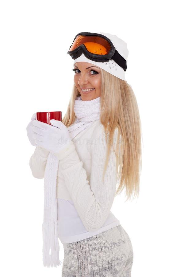 Den unga kvinnan skidar in exponeringsglas med den röda koppen royaltyfri foto