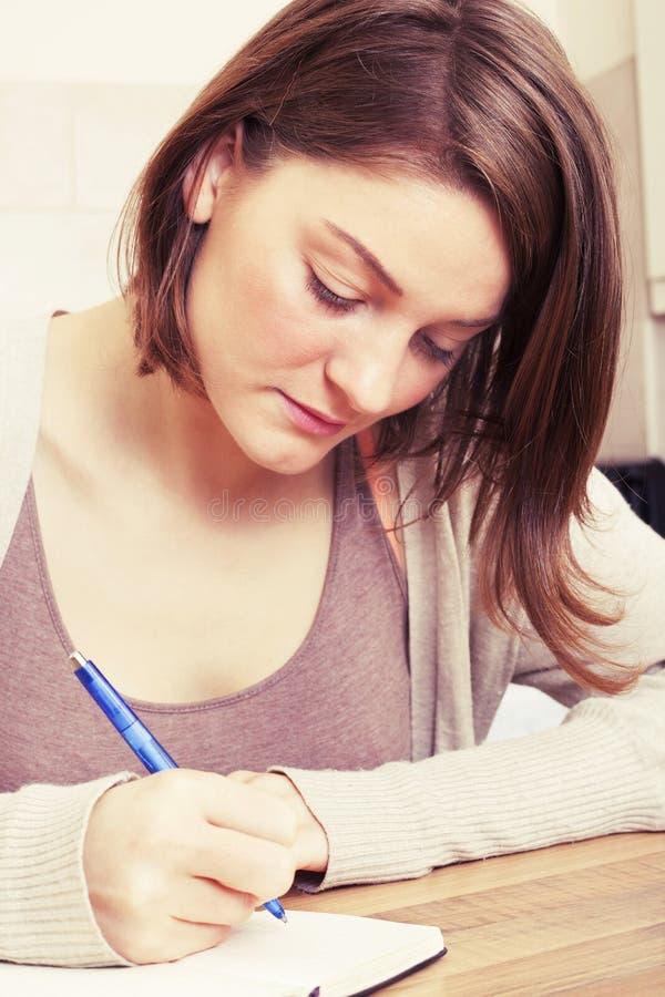 Den unga kvinnan skriver till den svarta dagboken arkivfoton