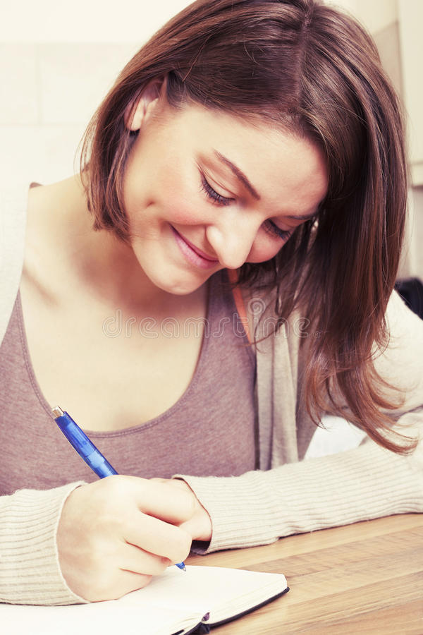 Den unga kvinnan skriver till den svarta dagboken fotografering för bildbyråer