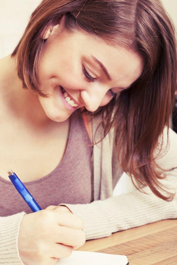 Den unga kvinnan skriver till den svarta dagboken royaltyfri bild