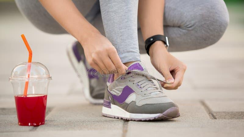 Den unga kvinnan snör åt flinar upp den sunda sportiga livsstilen arkivfoto