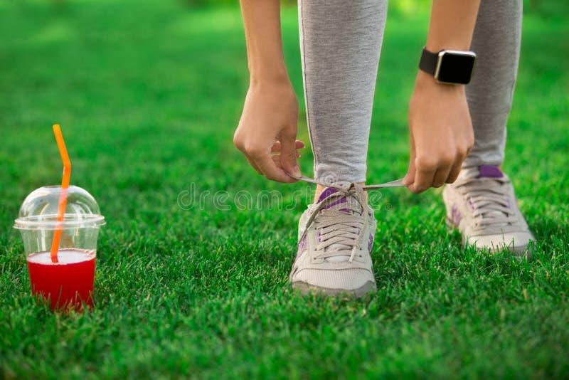 Den unga kvinnan snör åt flinar upp den sunda sportiga livsstilen royaltyfri bild