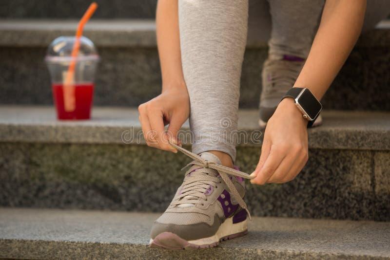 Den unga kvinnan snör åt flinar upp den sunda sportiga livsstilen arkivbild