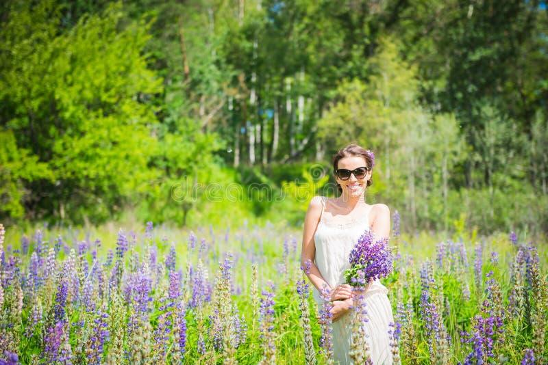 Den unga kvinnan som är lycklig, anseendet bland fältet av violetta lupines som ler, lila blommar Blåttsky på bakgrunden Sommar m royaltyfria bilder