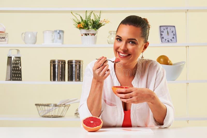 Den unga kvinnan som äter den sunda fruktdruvan för mellanmålet, bantar lunch arkivbilder