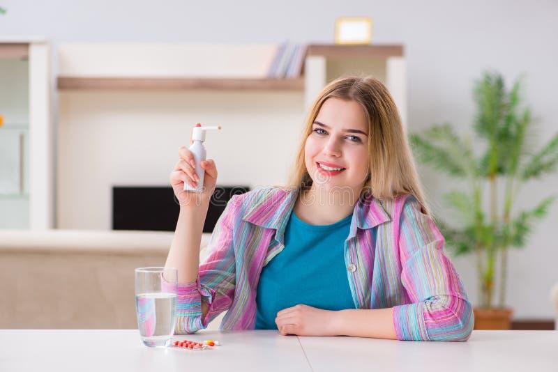Den unga kvinnan som använder inhalatoren för att klara av med astma fotografering för bildbyråer