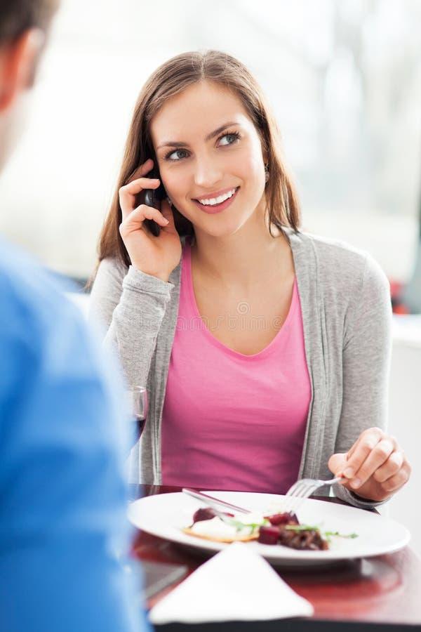 Kvinnan som använder mobil, ringer i restaurang royaltyfria bilder