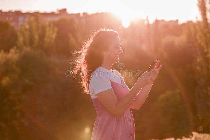 Den unga kvinnan som använder mobiltelefonen på solnedgången i, parkerar Guld- timme och teknologibegrepp arkivfoto