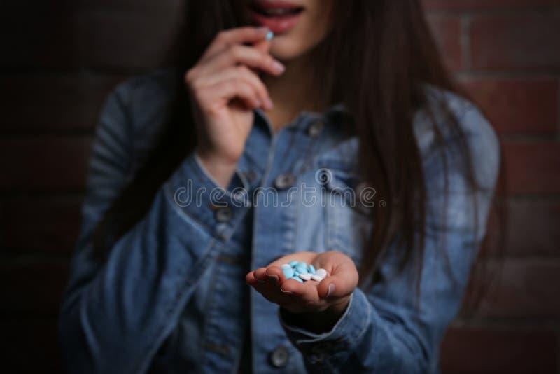 Den unga kvinnan som använder preventivpillerar för, begår självmord royaltyfri foto