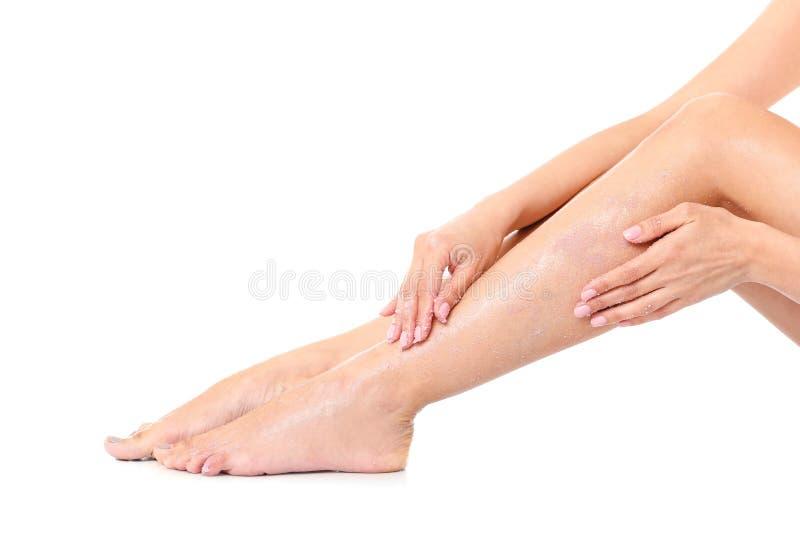 Den unga kvinnan som applicerar kroppen, skurar på benet fotografering för bildbyråer