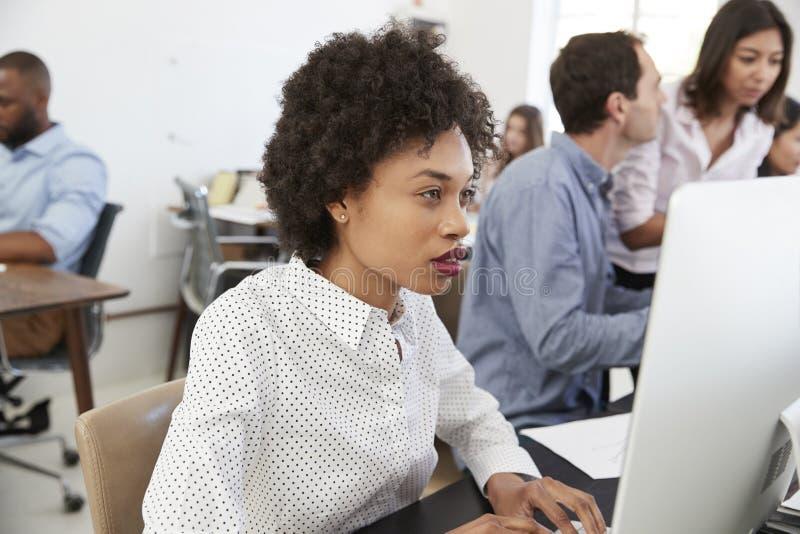 Den unga kvinnan som arbetar på datoren i ett upptaget, öppnar plankontoret royaltyfri bild