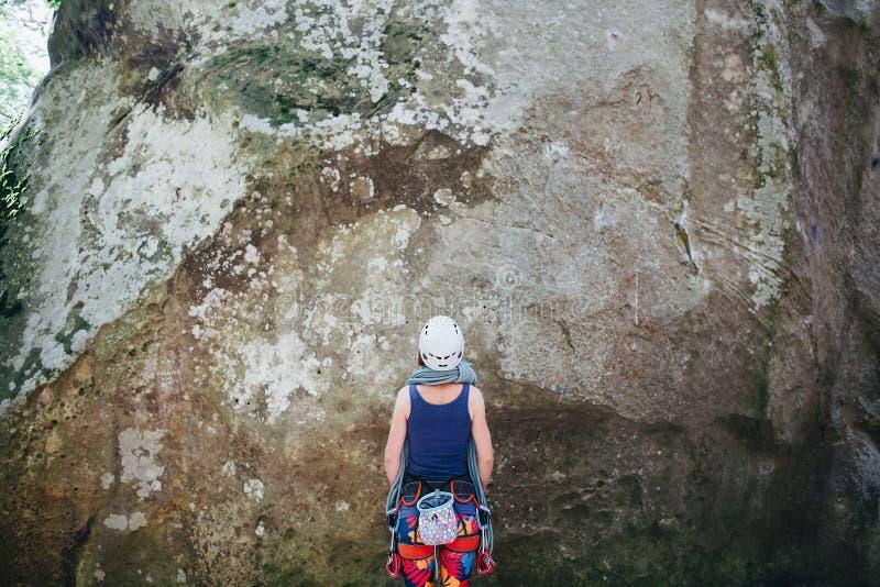 Den unga kvinnan som bär i klättringutrustning med repet som står av en sten, vaggar framme och förbereder sig att klättra arkivfoto