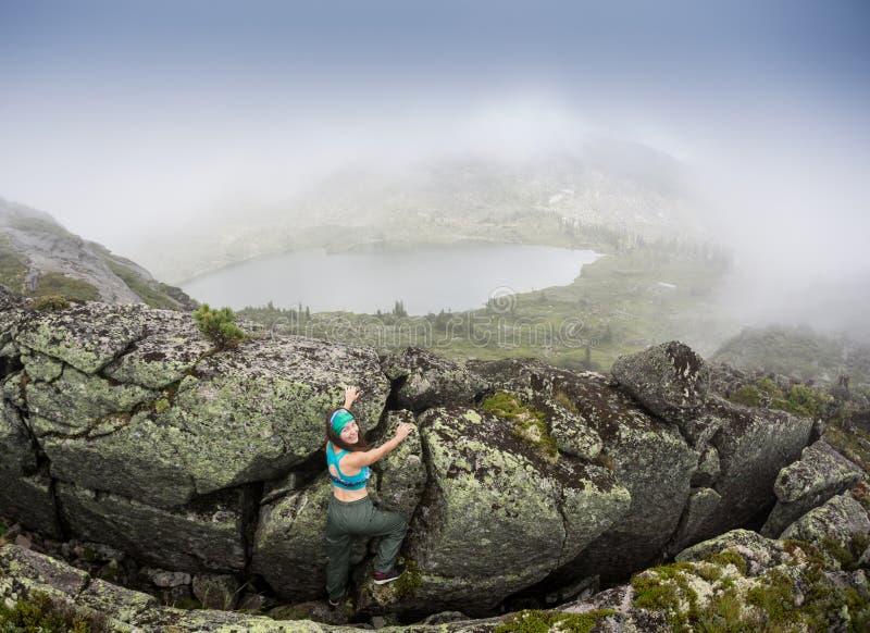 Den unga kvinnan som bär i klättringutrustning som står av en sten, vaggar framme utomhus- och att förbereda sig att klättra, den arkivbild