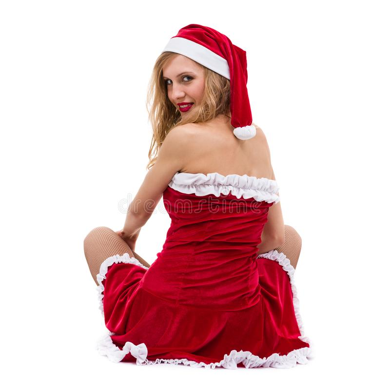 Den unga kvinnan som bär Santa Claus, beklär att posera mot isolerad vit arkivfoto