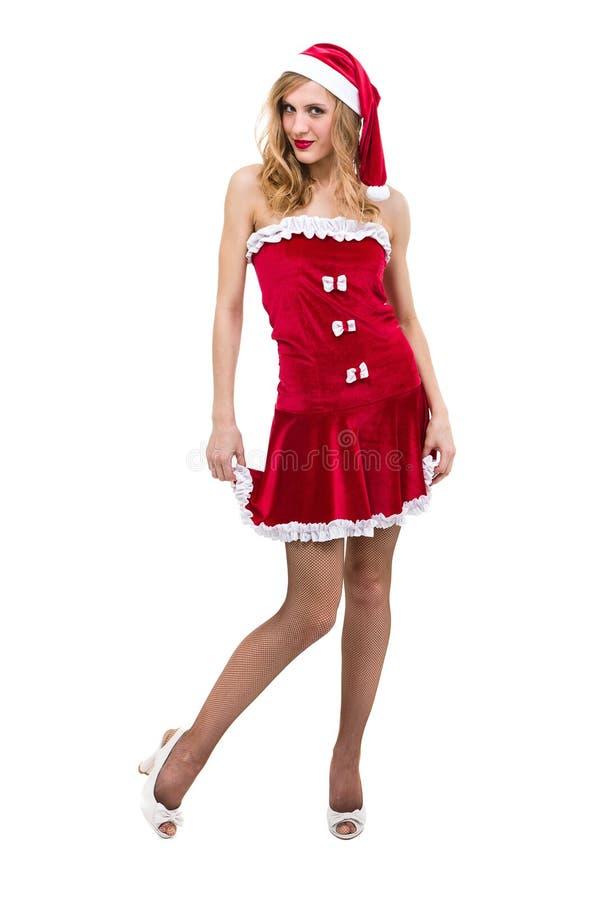Den unga kvinnan som bär Santa Claus, beklär att posera mot isolerad vit royaltyfri bild
