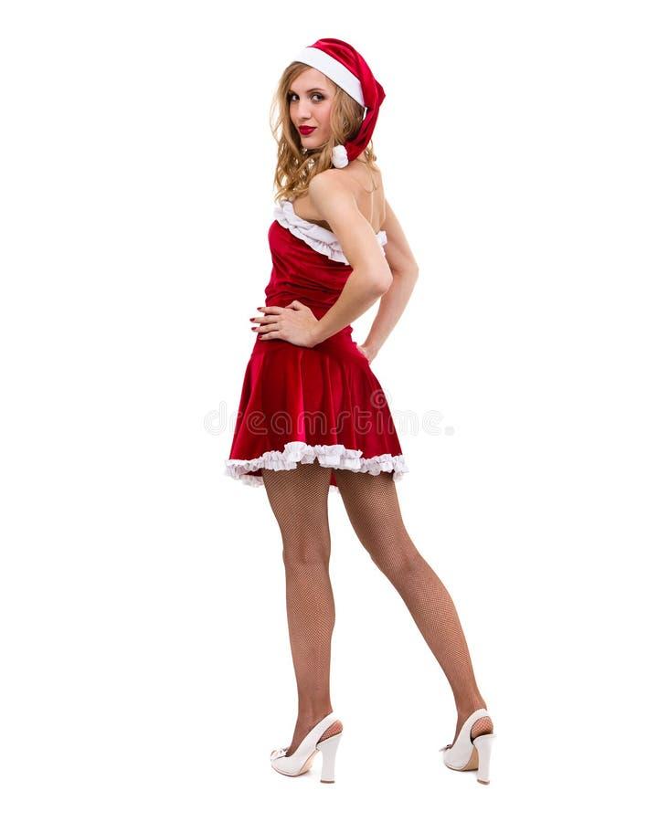 Den unga kvinnan som bär Santa Claus, beklär att posera mot isolerad vit royaltyfria foton