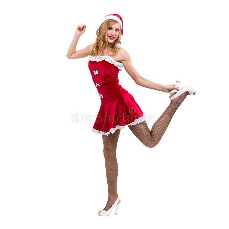 Den unga kvinnan som bär Santa Claus, beklär att posera mot isolerad vit royaltyfri fotografi