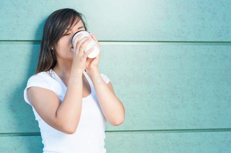 Den unga kvinnan som dricker kaffe från takeaway, rånar royaltyfri fotografi