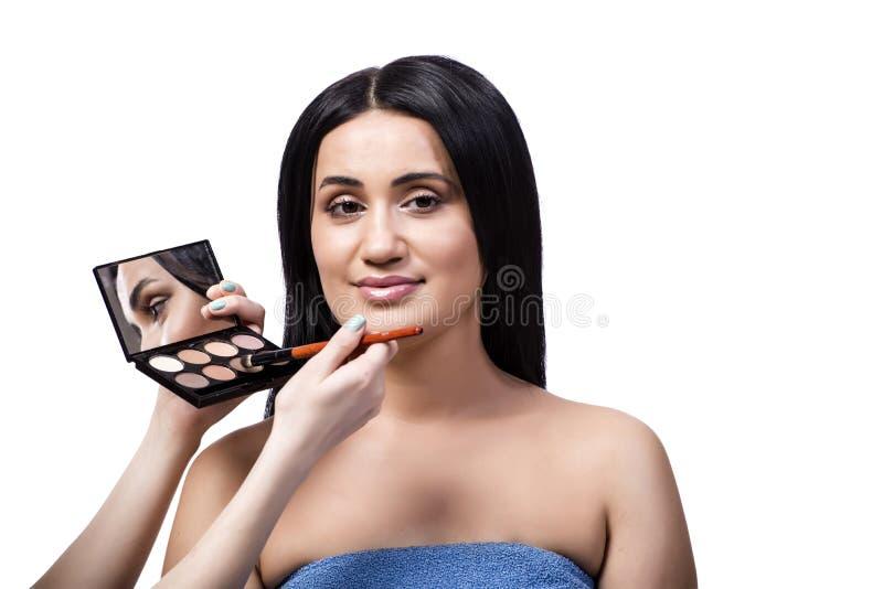 Den unga kvinnan som får smink isolerat på vit arkivfoto