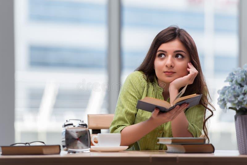 Den unga kvinnan som förbereder sig för skolaexamina royaltyfri foto