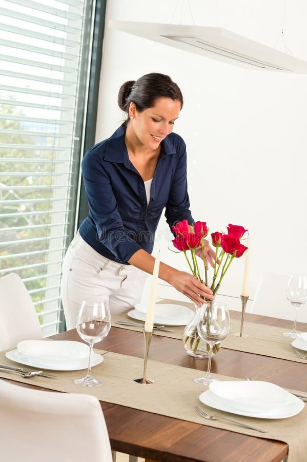 Den unga kvinnan som förlägger blommamatställe, bordlägger arkivfoto