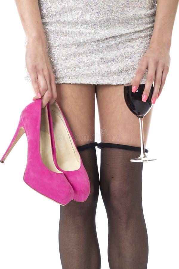Den unga kvinnan som festar med strumpan, rullade rymma ner höga häl och exponeringsglas av vin arkivbilder