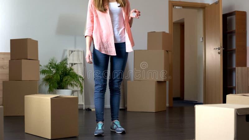 Den unga kvinnan som flyttar sig till den nya lägenheten som rymmer tangenter, packade upp saker omkring royaltyfri fotografi