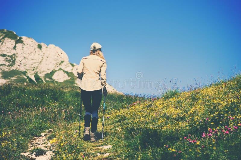 Den unga kvinnan som fotvandrar med trekking poler, reser livsstilbegrepp royaltyfria bilder