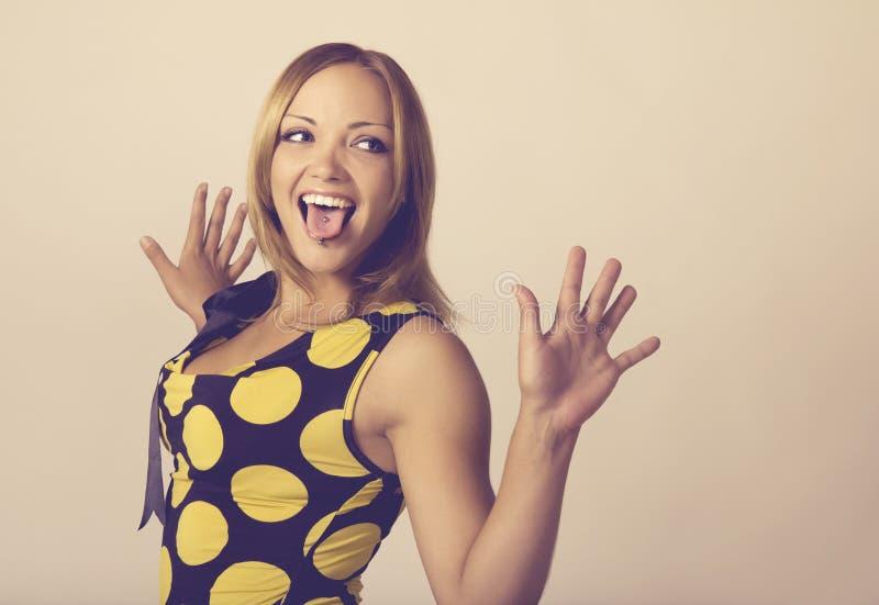 Den unga kvinnan som gör en rolig framsida, tonade i varmt royaltyfri foto