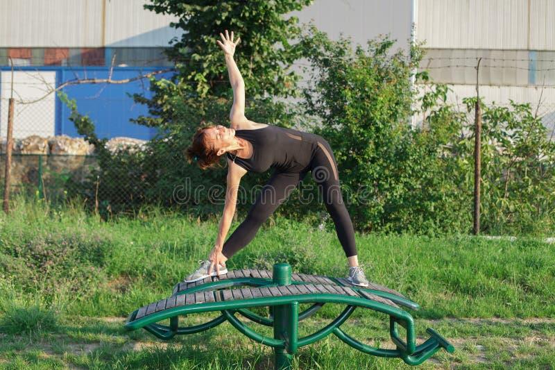 den unga kvinnan som gör triangelyoga, poserar utomhus royaltyfri fotografi