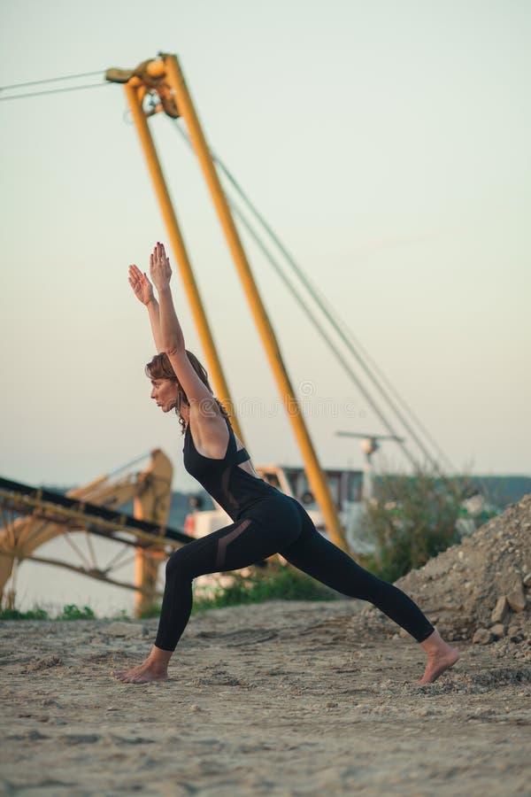 den unga kvinnan som gör variation av växande yoga, poserar royaltyfria foton