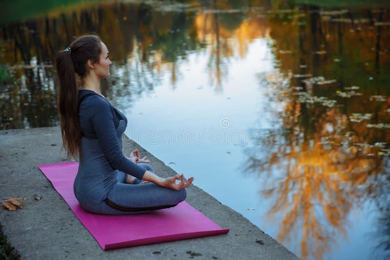 Den unga kvinnan som gör yoga, övar i höststadsparken Vård- livsstilbegrepp royaltyfria foton